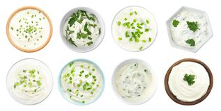 Set of delicious sour cream with herbs in bowls on white, top view. Set of delicious sour cream with herbs in bowls on white background, top view stock photos