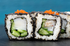 Set of delicious sushi rolls with white fish and cucumber in bla Royalty Free Stock Photo