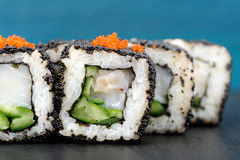 Set of delicious sushi rolls with white fish and cucumber in bla Stock Image