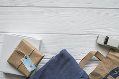 Set in denim craft style with space for text. White wooden background, bag, clothes, packed items Royalty Free Stock Images