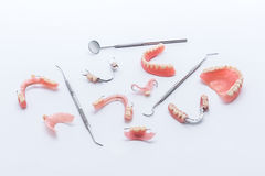 Set of dentures and dental tools on white background Royalty Free Stock Photography