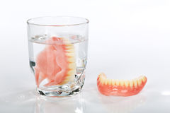 A set of dentures in a glass of water Royalty Free Stock Image
