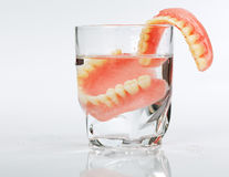 A set of dentures in a glass of water Royalty Free Stock Photos