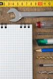 Set der Hilfsmittel und des Notizbuches auf Holz Stockbild
