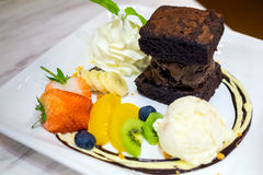 Set of dessert with ice cream, brownies, whip cream and fruits Stock Photos
