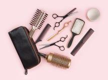 Set di strumenti dell'apprettatrice dei capelli con la borsa di cuoio su fondo rosa immagine stock libera da diritti