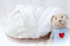Set of diapers for newborn in basket with love bear toy. Baby cl Stock Photo