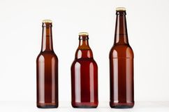 Set of different brown beer bottles 500ml and 330ml mock up. Template for advertising, design, branding identity on white wood ta. Ble stock images