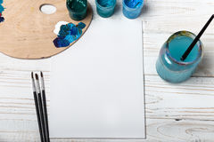 Set of different brushes and acrylic paints to paint scattered on a dark wooden table.Artist workplace background.Art tools.Creati. Vity, visual art concept stock image