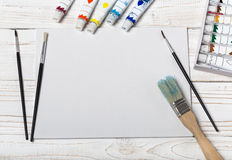 Set of different brushes and acrylic paints to paint scattered on a dark wooden table.Artist workplace background.Art tools.Creati. Vity, visual art concept royalty free stock photo