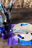 Set of different brushes and acrylic paints to paint scattered on a dark wooden table.Artist workplace background.Art tools.Creati. Vity, visual art concept royalty free stock photography