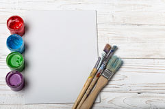 Set of different brushes and acrylic paints to paint scattered on a dark wooden table.Artist workplace background.Art tools.Creati. Vity, visual art concept stock photo
