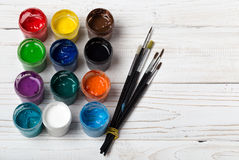 Set of different brushes and acrylic paints to paint scattered on a dark wooden table.Artist workplace background.Art tools.Creati. Vity, visual art concept royalty free stock images