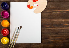Set of different brushes and acrylic paints to paint scattered on a dark wooden table.Artist workplace background.Art tools.Creati. Vity, visual art concept royalty free stock photos