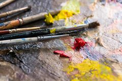 Set of different brushes and oil paints to paint scattered on a dark wooden table top view stock images