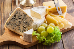 Set of different cheeses. On a chopping board Stock Photography