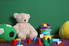 Set of different child toys on floor. Against color wall royalty free stock image
