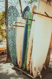 Set of different colorful surf boards in a stack. Available for rent on the beach. Vertical surfboards, vintage color tone effect stock photo