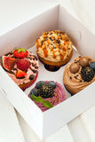 Set of different cupcakes decorated with fresh berries. In white paper box Royalty Free Stock Photo