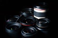 Set of different DSLR lenses on a dark background. Dramatic lighting stock photo