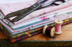 Set of different fabric, wooden thread spools and tailor scisso Stock Images