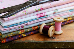 Set of different fabrics, wooden thread spools and tailor scisso Stock Images