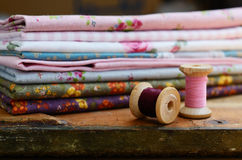 Set of different fabrics and wooden thread spools Stock Photography