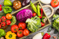 Set of different fresh raw colorful vegetables in the wooden tray. Light background Royalty Free Stock Photos