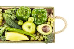 Set of different green fresh raw vegetables and fruits in the wooden tray. Isolated on white Stock Photography