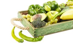 Set of different green fresh raw vegetables and fruits in the wooden tray. Isolated on white Stock Image