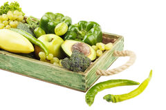 Set of different green fresh raw vegetables and fruits in the wooden tray, isolated Royalty Free Stock Photos