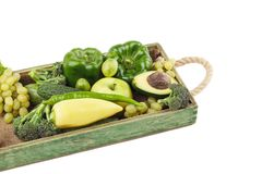 Set of different green fresh raw vegetables and fruits in the wooden tray. Isolated on white Royalty Free Stock Photos