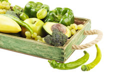 Set of different green vegetables and fruits in the wooden tray, isolated Royalty Free Stock Photos