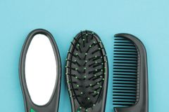 A set of different hair brushes and a mirror in one style on a bright blue background. view from above stock photo