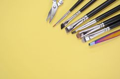 A set of different makeup artist brushes and scissors lie in a corner with copyspace for text on yellow color stock images