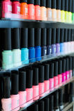 Set of different nail varnishes on shelves in cosmetic store Stock Images