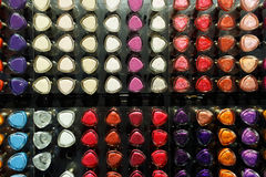 Set of different nail varnishes on shelves in cosmetic store Stock Photos