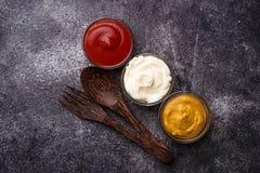 Set of different sauces: mustard, ketchup, mayonnaise. Stock Photos