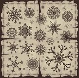 Set of different snowflakes over old page Stock Images