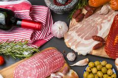 Set of different Spanish appetizer, like fuet, jamon, chorizo, bacon and lomo embuchado with red wine and olives. Set of different Spanish appetizer, like fuet Royalty Free Stock Photos
