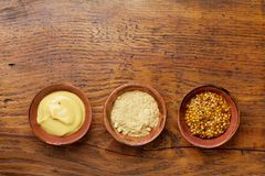 Set of different spices. French mustard, dijon mustard and powder on wooden rustic table top view. Set of different spices. French mustard, dijon mustard and Stock Photos