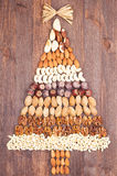 Tree nuts. Set of different varieties of nuts in the form of a tree with a gold bow at the top Stock Photo