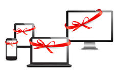 Set of digital devices with gift ribbons and bow. Royalty Free Stock Images