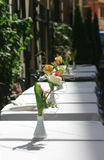 Set for dinner. A row of tables outside a restaurant set ready for dinner on the streets of Rome in Italy. Fresh flowers in small white pots seton white table stock image
