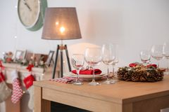 Set of dinnerware and Christmas wreath. On table indoors stock photos