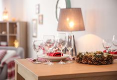 Set of dinnerware and Christmas wreath. On table indoors stock photography