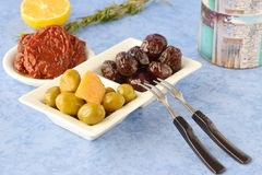 A set of dishes of greek cuisine: olives, sun dried tomatoes, lemon, beetroot, jar with olive oil and traditional dry stock photography