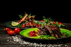 A set of dishes with pork ribs grilled with a in sour sweet berry sauce served with green seedlings served. Tasty snack. concept royalty free stock photos