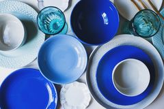 Set of dishware in blue tones. Ceramic plates and wine glasses. Top view royalty free stock images