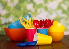 Set of disposable plastic tableware on light green background royalty free stock photos